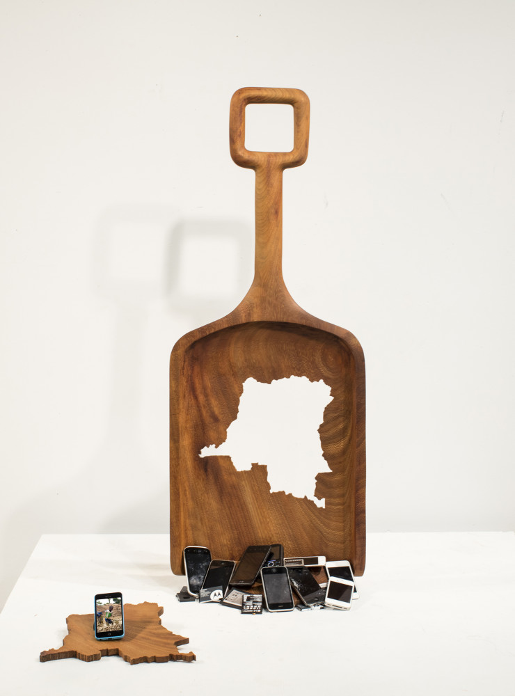 L'appel des enfants du Congo, 2016. Iroko wood, cell phones. Dimensions 120 x 60 x 8 cm (shovel only). This oversized wooden shovel of rare wood coming from the Congo is pierced by the geographical form of the country. A holed shovel and therefore use less to represent the Democratic Republic of Congo which is the main supplier of the necessary ore to the batteries of our cellular and laptop computers. Illegal mines where children work. Reality denounced by video images broadcast by one of the phones.